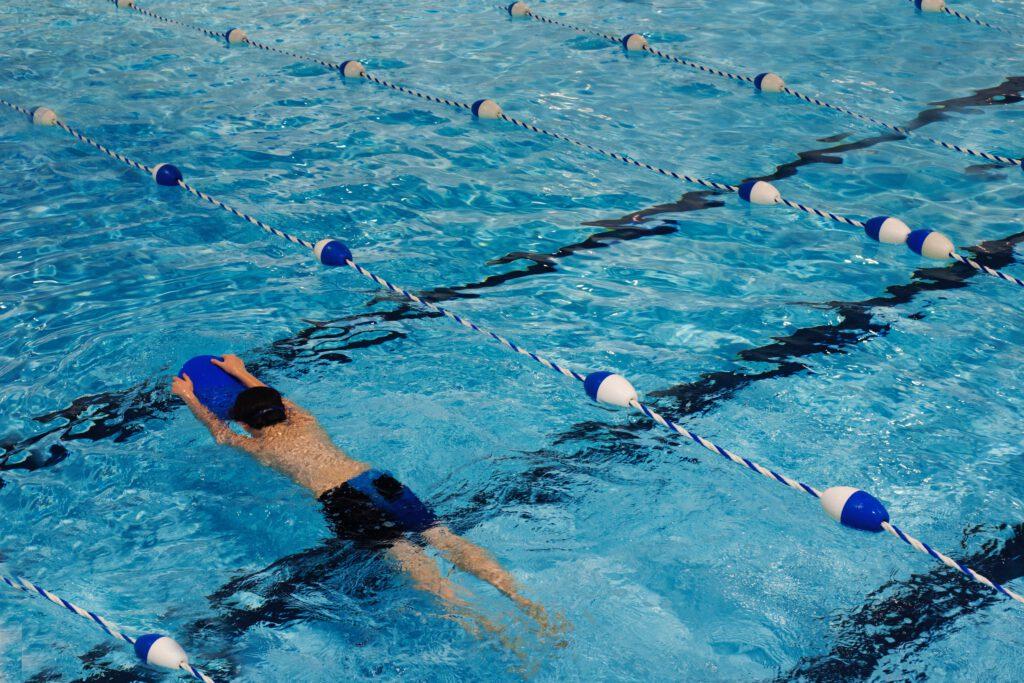 Ein einzelner Junge im Wasser, wie er gerade am Schwimmunterricht teilnimmt.