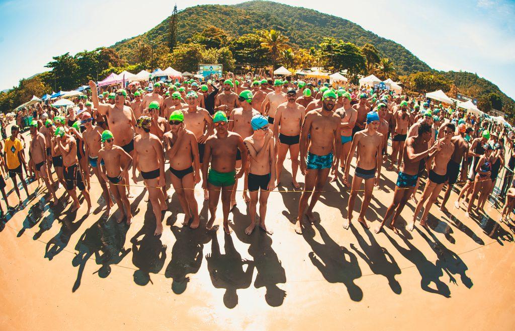 Eine Gruppe von Männern, die darauf wartet, endlich ins Wasser zu können und mit dem Schwimmen zu starten.