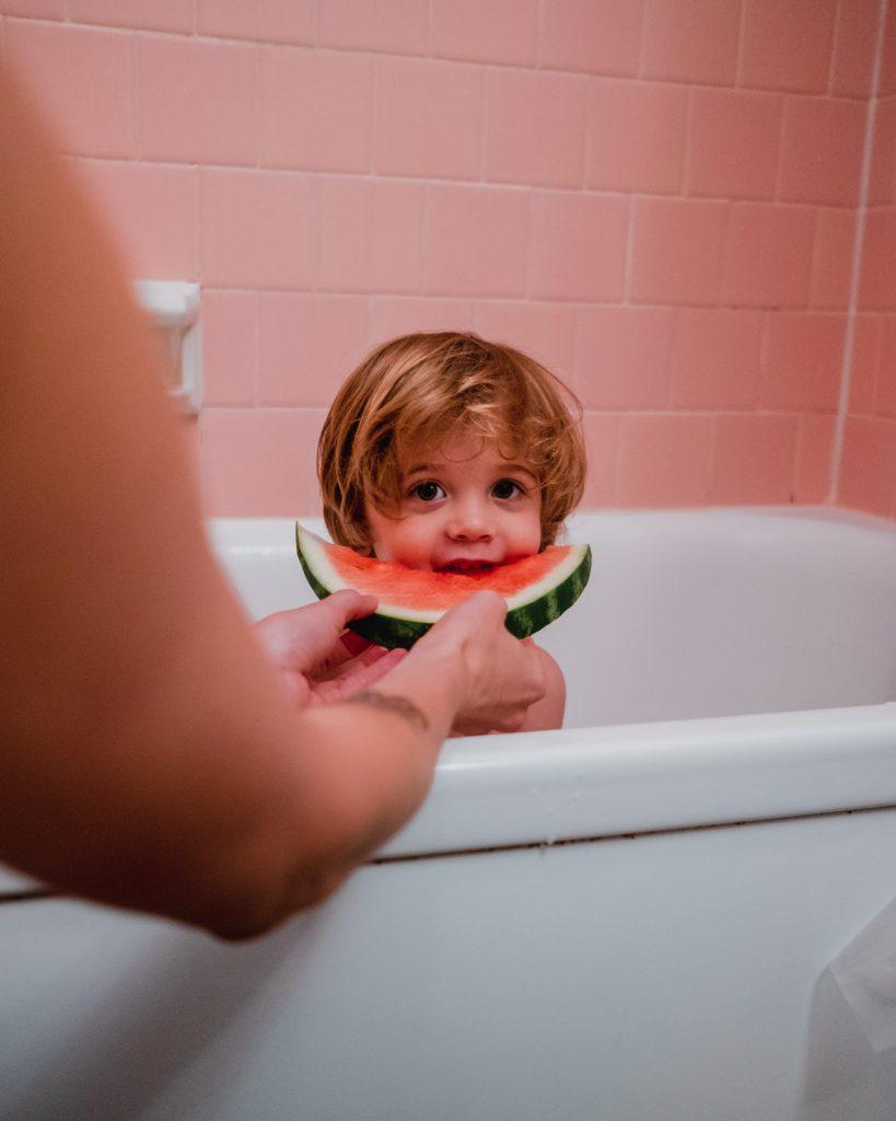 Kind sitzt in der Badewanne während des Kurses Schwimmenlernen zuhause