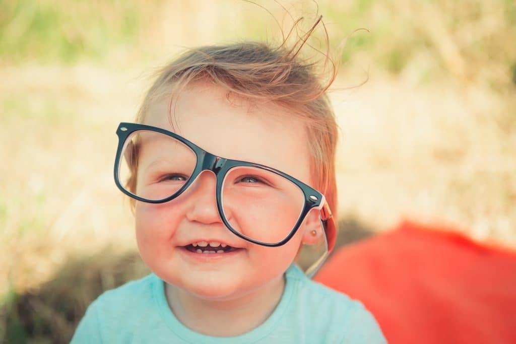 Kind mit einer normalen Brille, die schief auf dem Gesicht sitzt, ohne Schwimmbrille für Kinder