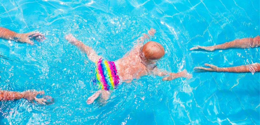 Baby swimming with parents in clearblue water