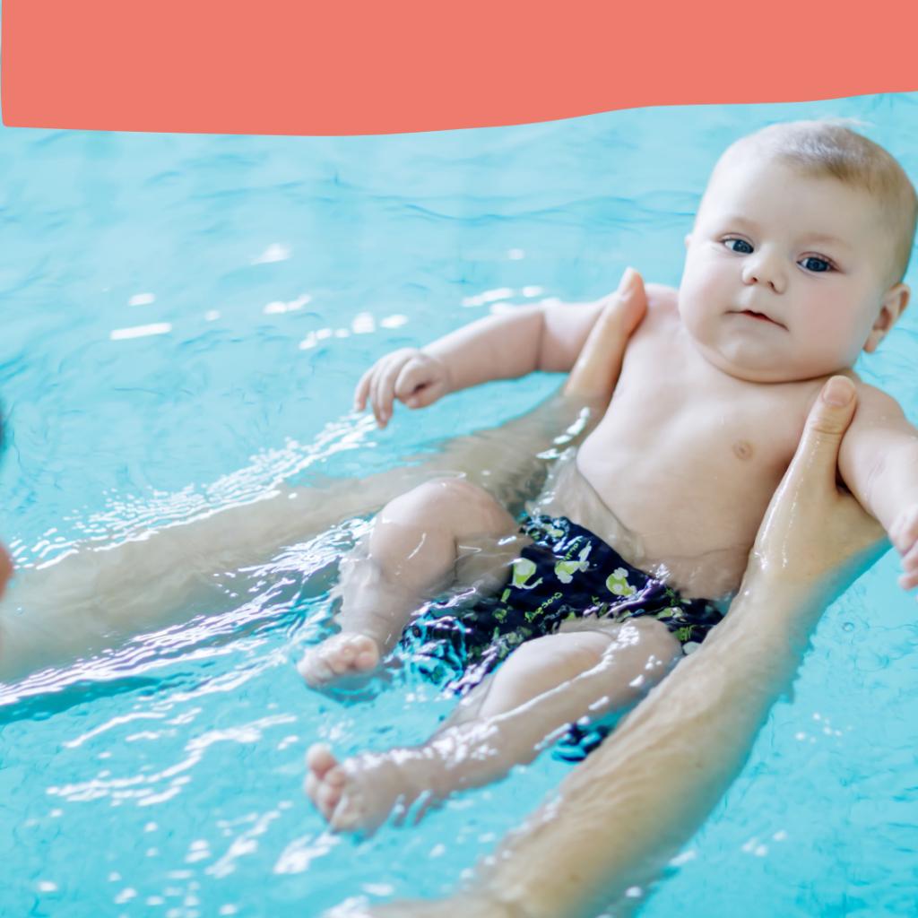 Baby beim Babyschwimmen in den Armen seiner Mutter